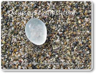 Pale blue sea glass stands out against the darker rocks